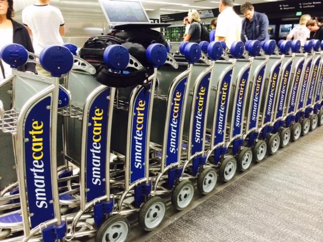 Os carrinhos do Smart Carte estão enfileirados ao lado das esteiras de bagagem.