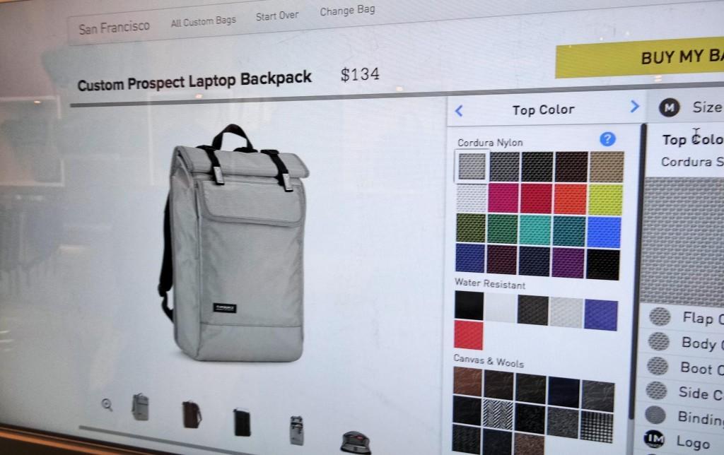 Dentro da loja tem um painel enorme mostrando a página da internet deles, com as opções de customização.